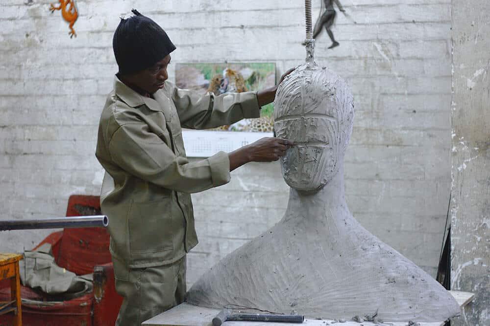 man sculpting clay model