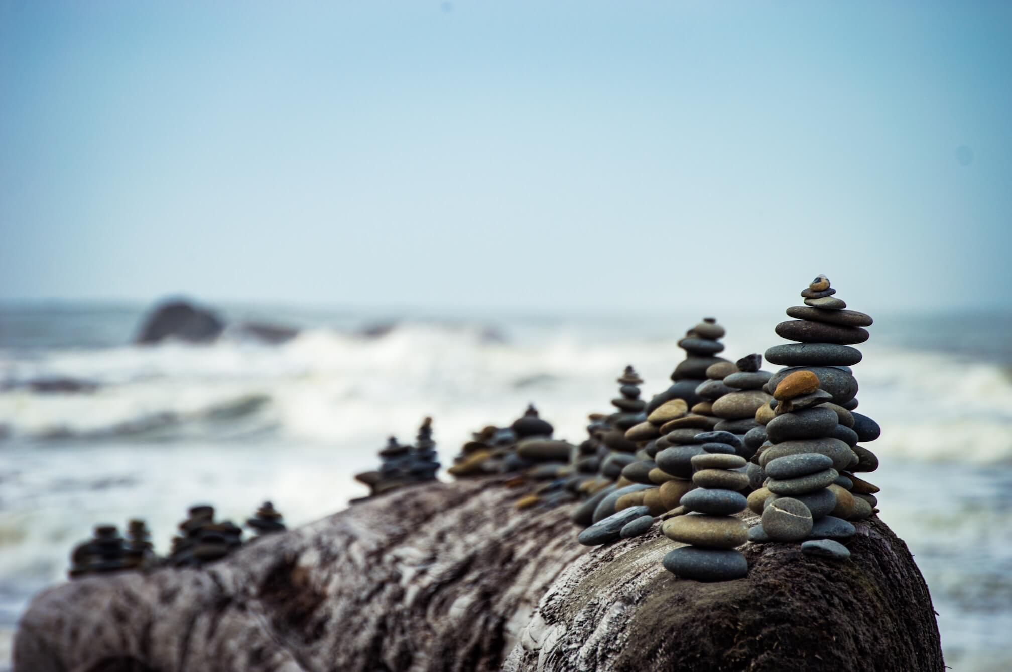 piles of pebbles balanced in front of ocean
