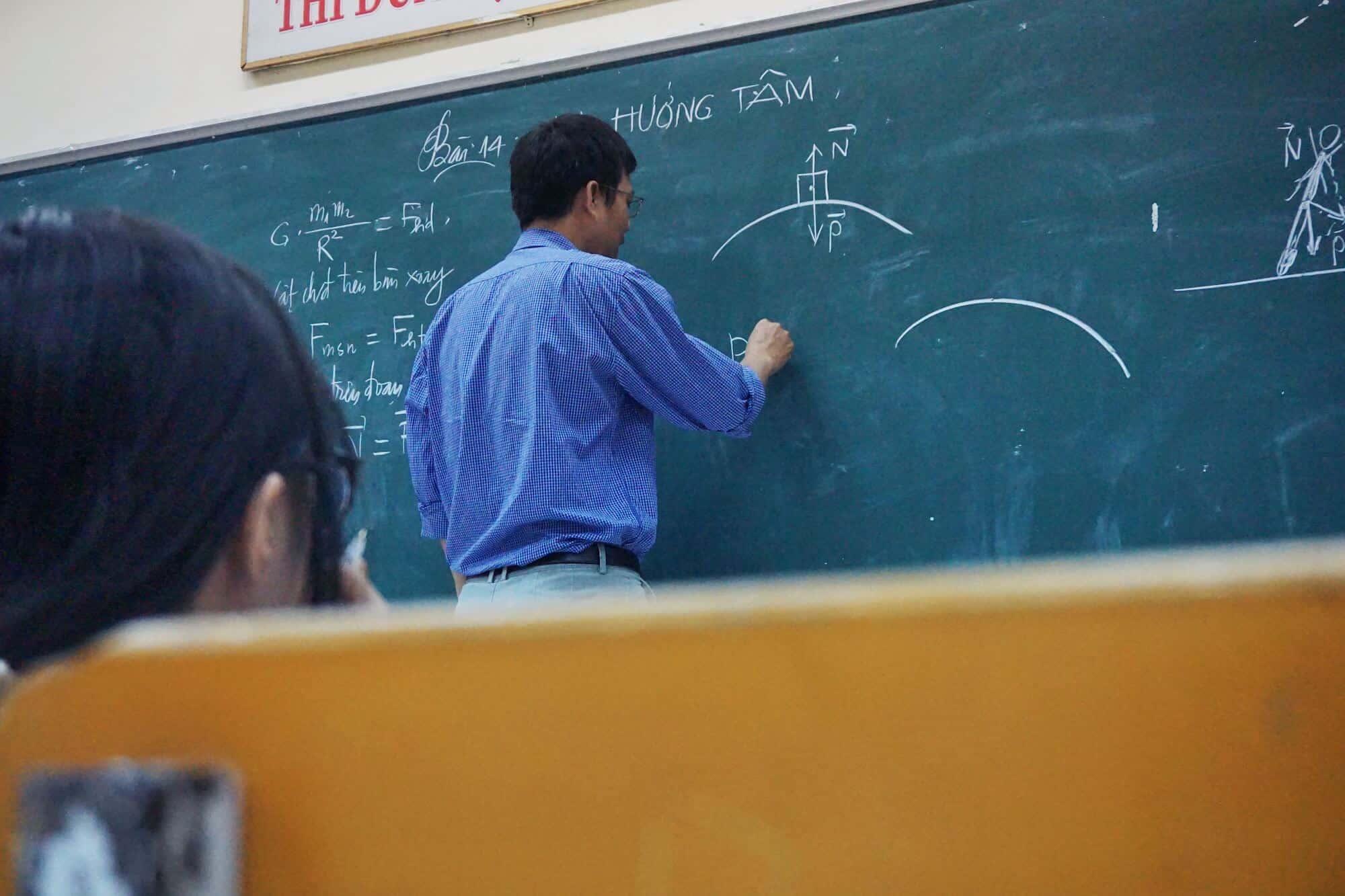 teacher writing physics problem on the board