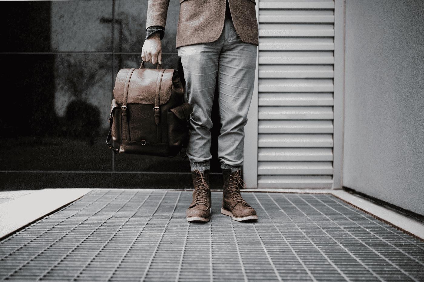 man holding leather bag