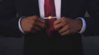 hands straightening necktie