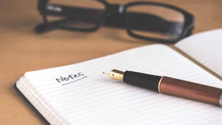 glasses and fountain pen near open notebook