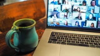 Coffee mug on table next to MacBook with Zoom call