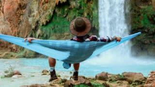 Man relaxing in hammock in front of waterfall
