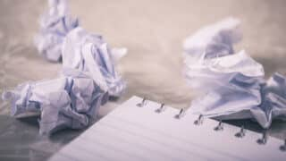 Crumpled pieces of paper next to notepad