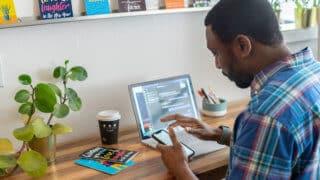 Man checking phone while working at laptop