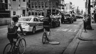 Cyclists riding past cars on Chicago street